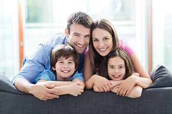 Happy Couple with Two Children on a Couch